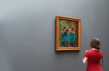 a woman in an art gallery ponders a degas painting