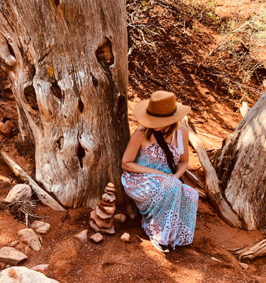 a woman in cowboy hat crouches by a tree in the desert