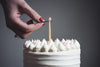 a woman lits a single birthday candle