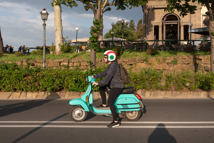 A Woman On A Turquoise Moped On A Highway