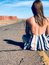 a woman sat in the middle of a highway through the desert