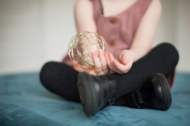 A Woman Sat On A Bed Holds Out A Gold Mesh Ball