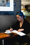 a woman sits alone in a coffee shop writing
