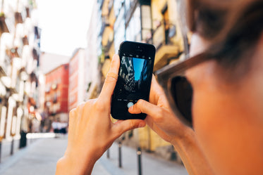 a woman snaps a photo on her mobile phone up a sunny street