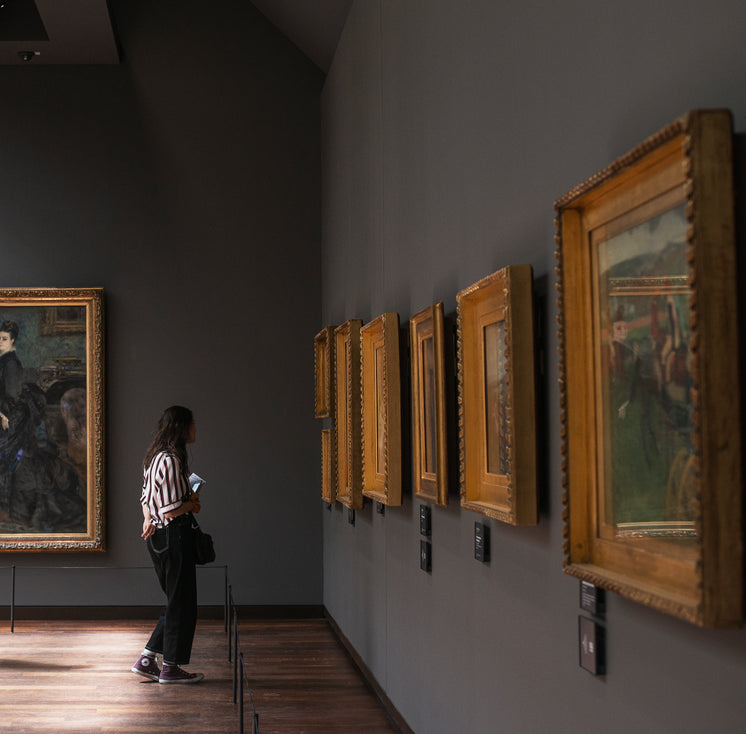 A Woman Stands In An Art Gallery In Front Of Paintings