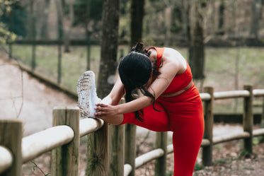 a woman stretches outdoors against a wooden fence