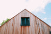 a wooden house with attic window under cloud-studded sky