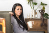 a young woman leans back on a couch with a coffee