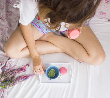 a young woman sits cross-legged on a bed eating macaroons
