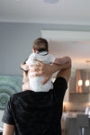 adult faces the wall and holds a baby on shoulders