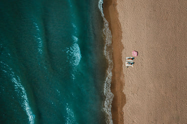aerial view of two women sitting on sandy beach