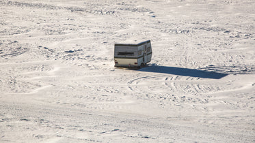 an abandoned camper trailer parked in an open snow-covered field