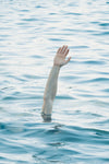 an arm reaches up over the blue water