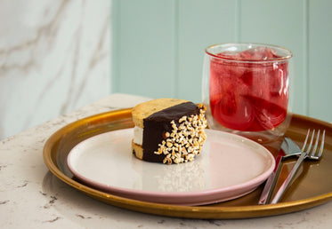 an ice cream sandwich and a glass of juice on a tray