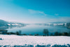 an icy blue lake framed by snowy sides