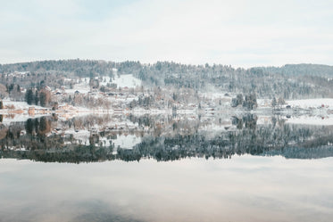 an icy lake under snowy and snowy hills under frosty sky