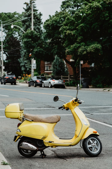 an italian summery yellow moped parked on a street