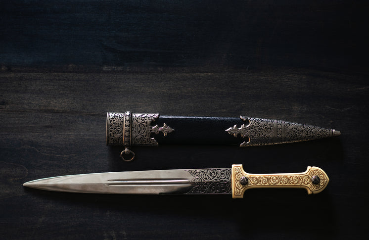 An Ornate Dagger And Sheath On A Wooden Table