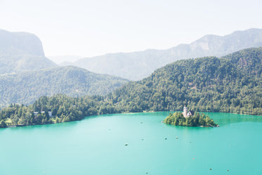 aqua blue water surrounded by tall green hilly trees