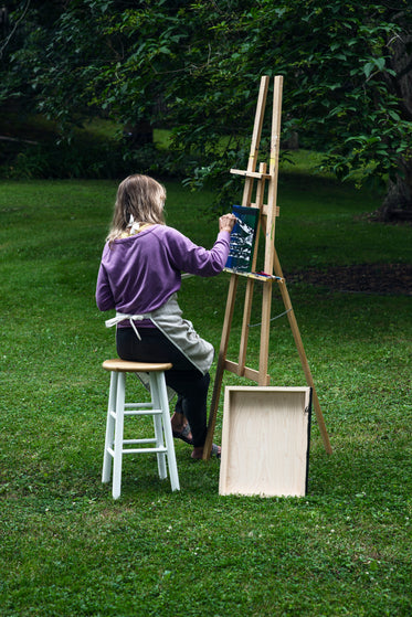 artist sits outdoors and paints at an easel