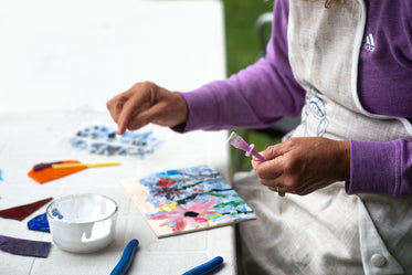 artist works on a floral mosaic with white glue