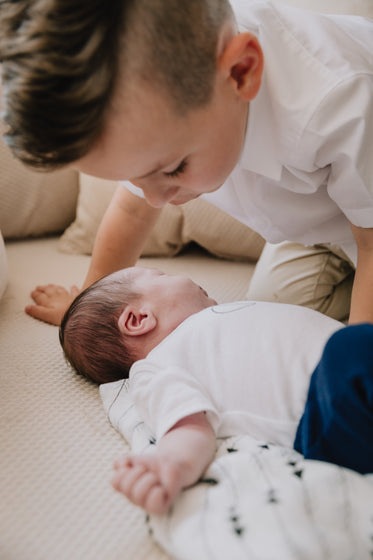 baby lays on a blanket with a child saying hello