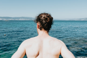 back of a person looking out to the choppy ocean