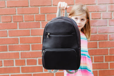 back to school holding out backpack