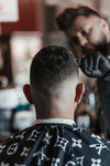 barber inspects his work of a clean haircut
