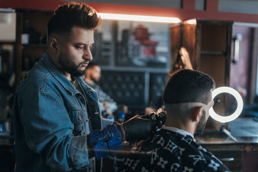 barber uses clippers to line up hair