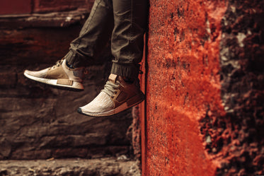 beige trainers in front of red wall