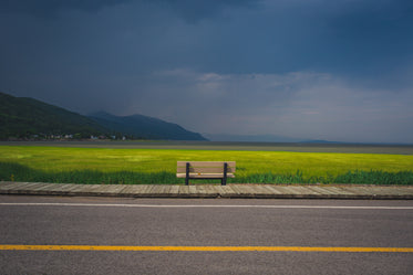 bench overlooking farm field and oncoming storm