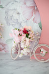 bike covered in flowers leans against a floral wall