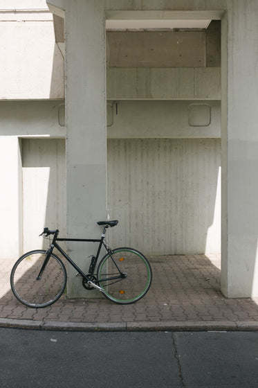 bike sits against concrete column