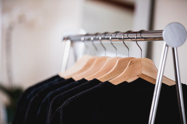 black and blue clothing on a rack in a sunlit shop