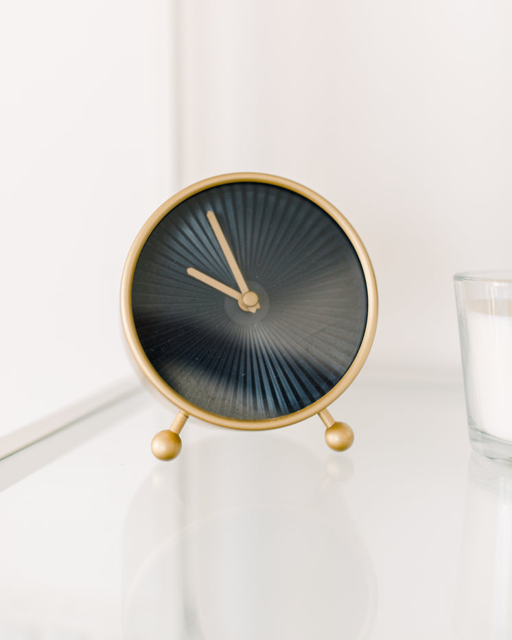 Black And Gold Clock Sits On A White Table