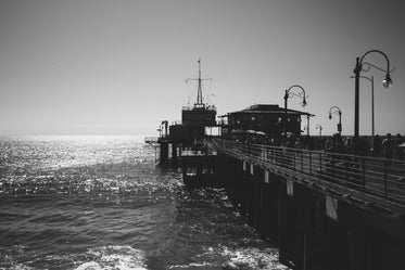 black and white busy pier overlooking the water