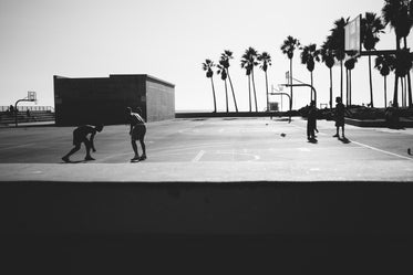 black and white people playing basketball near beach