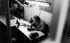 black and white photo of a person sitting by sewing machine