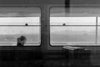 black and white photo of a person sitting in a window