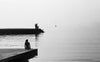 black and white photo of people on a cement shore by still water