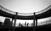 black and white photo of people walking in a bridge