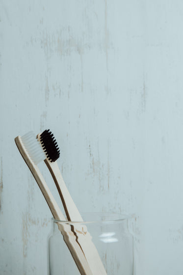 black and white wooden toothbrushes in a glass cup