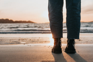 black boots and legs on a sandy beach at sunset