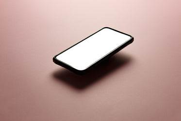 black cellphone floats above pink background