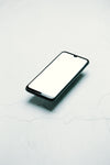black cellphone floats over a white surface