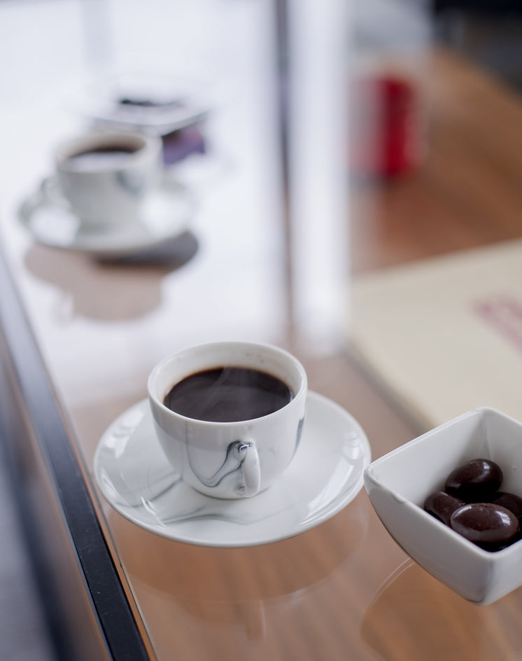 Black Coffee Accompanied By Square Bowl Of Olives