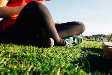 black leggings and green sneakers in a summery park