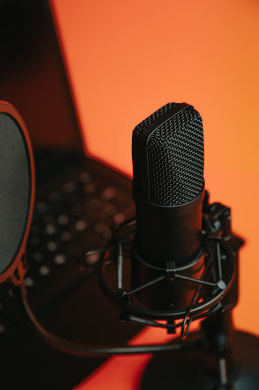 black microphone on a stand reflecting orange light
