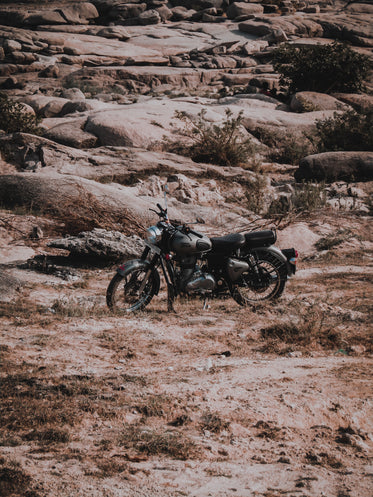 black motorcycle parked with a stone hill behind
